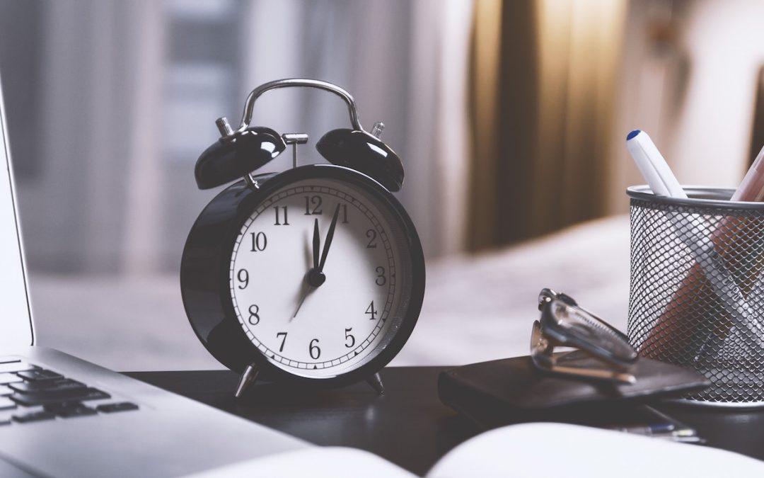 Wecker steht neben einem Notebook