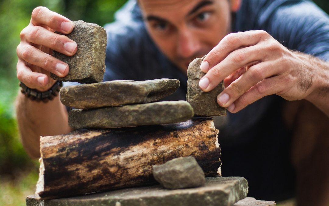 Mann stapelt Steine