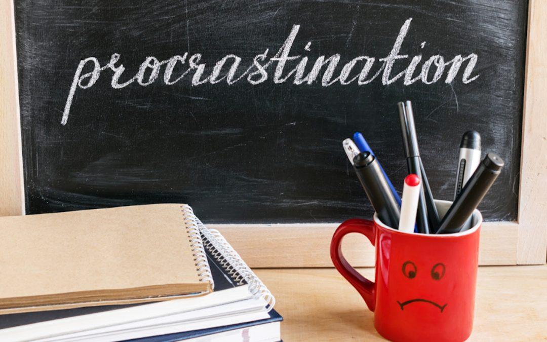 Tafel mit Aufschrift procrastination mit rotem Becher
