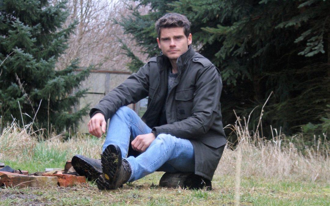 Björn Kern sitzend an einer Feuerstelle
